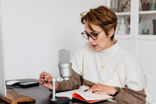 Female narrator in glasses reading out loud from book while sitting at desk with microphone and recording audiobook in cozy study