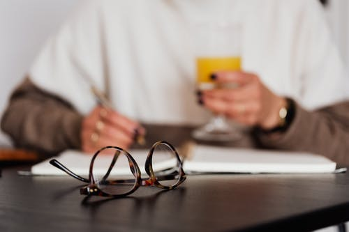 Crop blurred female in stylish sweater with glass of orange juice sitting at table with eyeglasses and writing in notebook