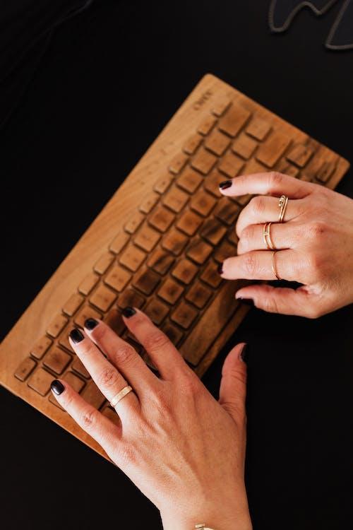 Crop woman typing on wireless keyboard