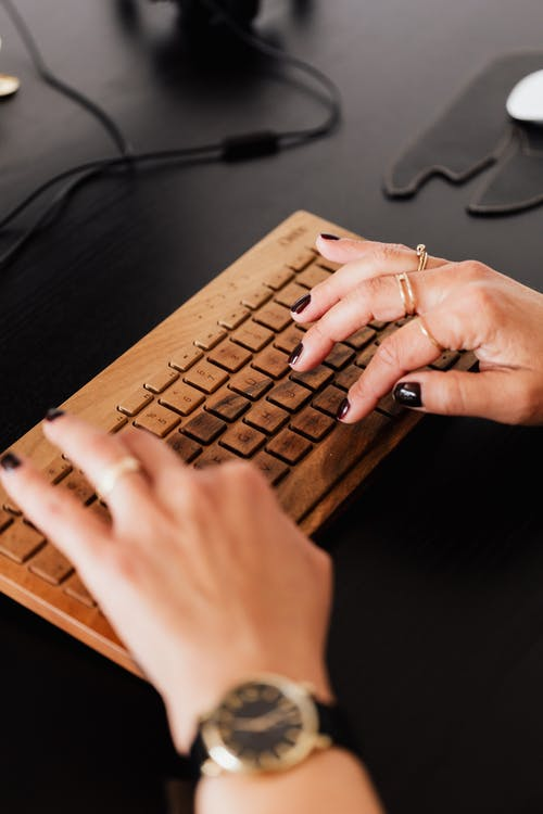 Crop woman typing on modern computer keyboard