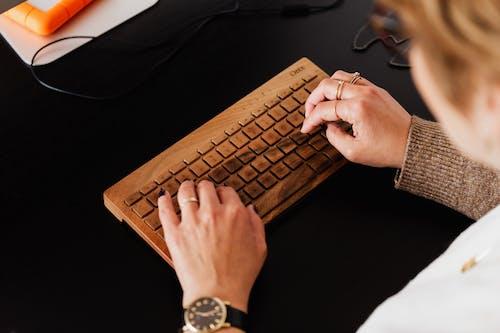 Crop woman typing on modern wireless keyboard