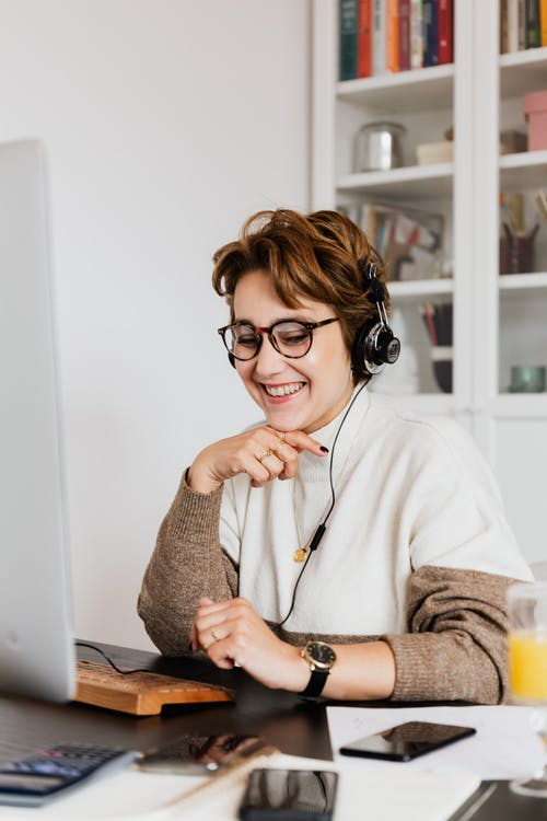 Smiling happy female in eyeglasses and wired headphones working on modern computer in contemporary light workspace in daytime