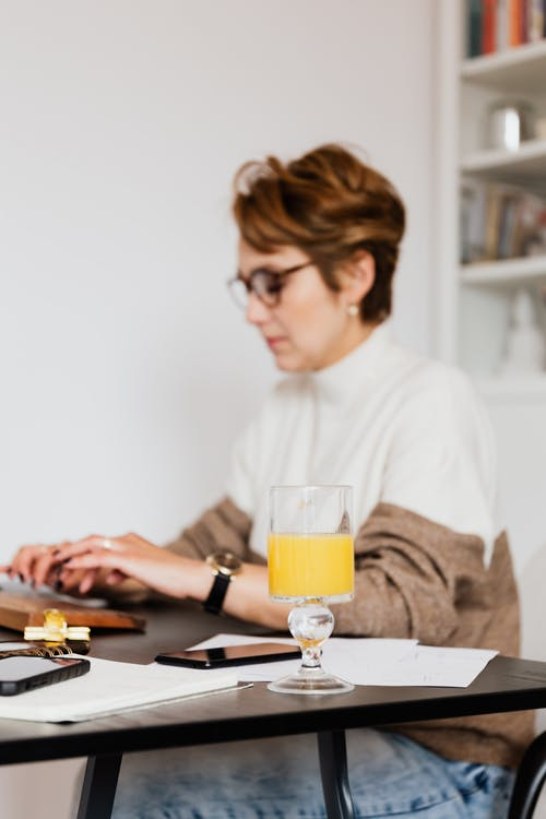 Side view pensive concentrated blurred female in trendy wear typing on computer keyboard while working at desk with papers and glass of fresh orange juice
