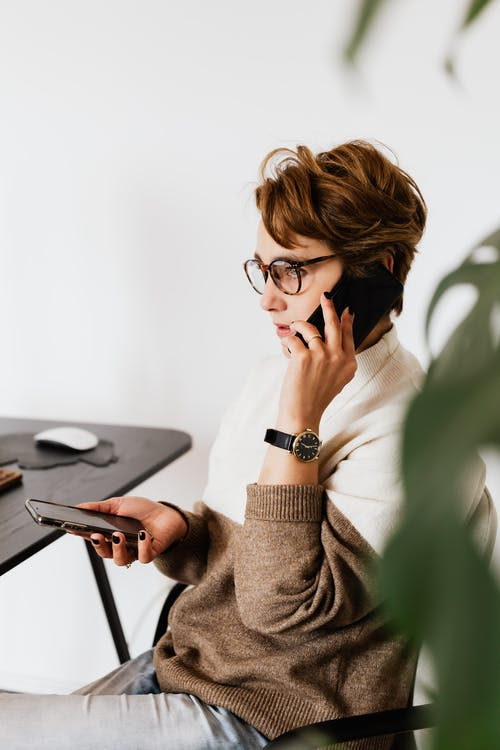 Concentrated woman in eyeglasses talking on smartphone
