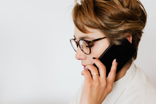 Thoughtful adult woman talking on smartphone