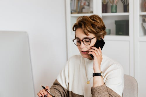 Focused adult woman talking on smartphone during work in office