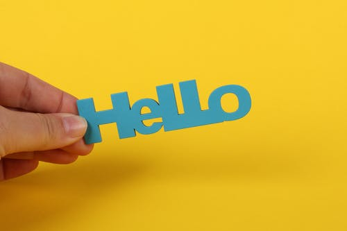 Free stock photo of blue and yellow, hand holding wooden text, Hello, yellow background