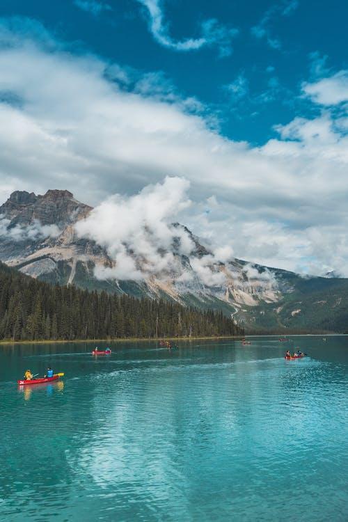 Photo of People Riding Kayak on Lake Across Mountain