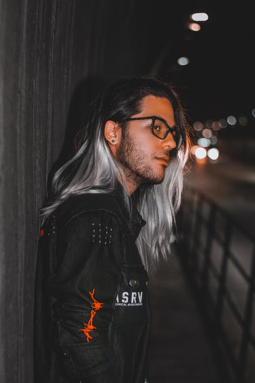 Man in Black Leather Jacket Standing Beside Black Metal Fence during Night Time