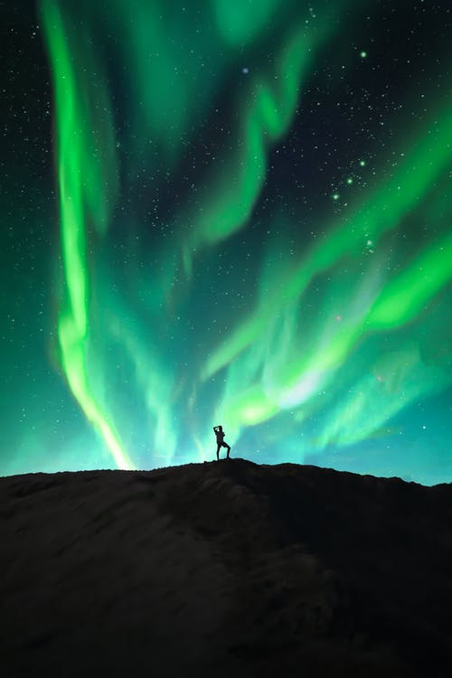 Silhouette of a Person under the Beautiful Northern Lights