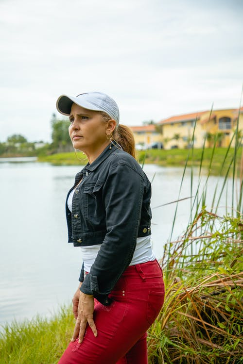 Woman in Black Jacket and Red Pants Standing Near Body of Water