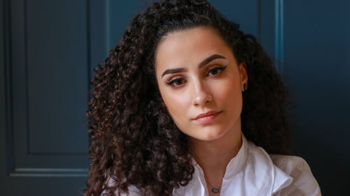 Charming woman with curly hair looking at camera