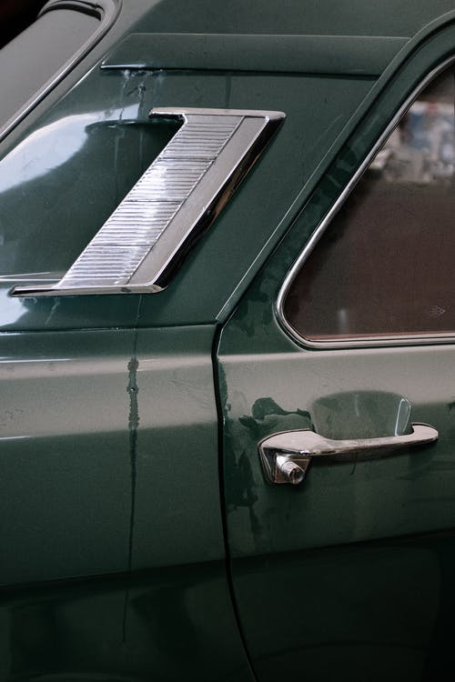 Green Car With Brown and White Door Lever