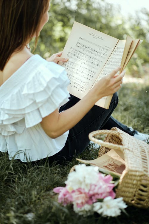 Woman in White Top Reading Music Book