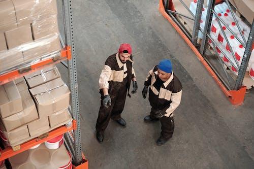 2 Men Standing in a Warehouse Talking