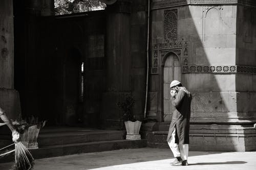 Monochrome Photo of a Man Walking Towards the Mosque