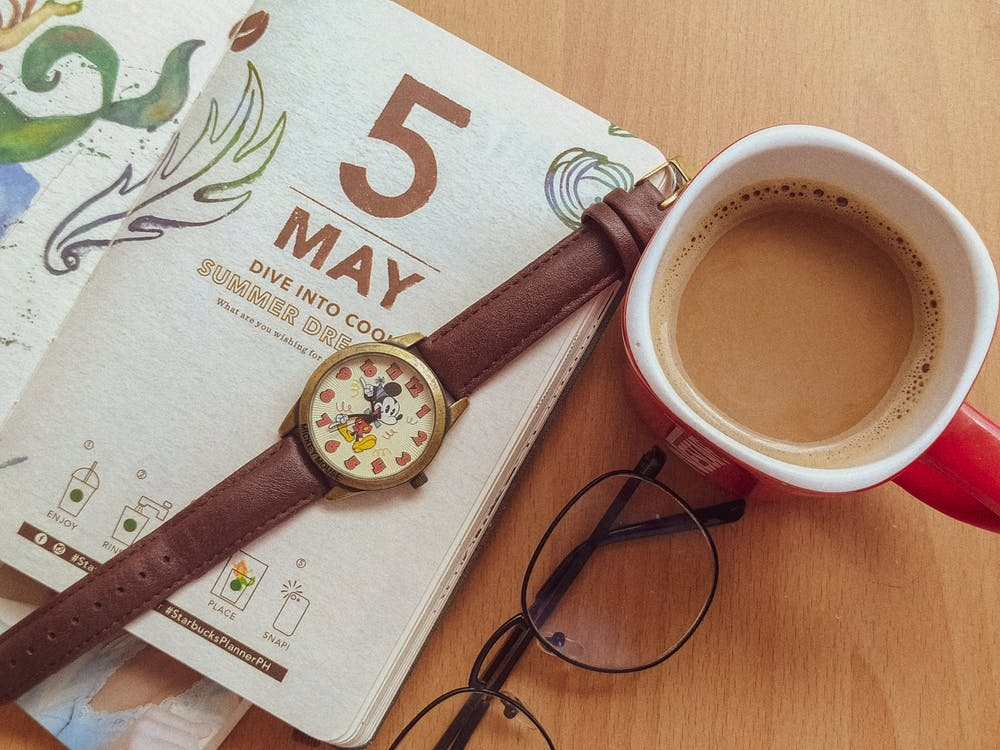 Top view of cup of fresh coffee and notepad arranged on table with wristwatch and eyeglasses in creative workspace of freelancer