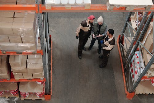 Men Standing in a Warehouse Talking
