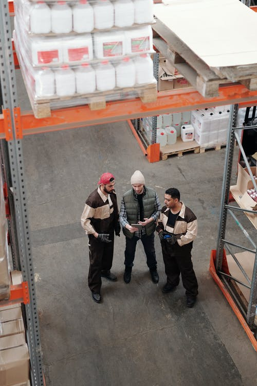 3 Men in Black Pants and Red and White Cap Standing on Gray Concrete Floor