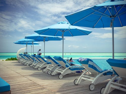 Collection of contemporary deck chairs under umbrellas located on wooden terrace in front of blue sea in summer