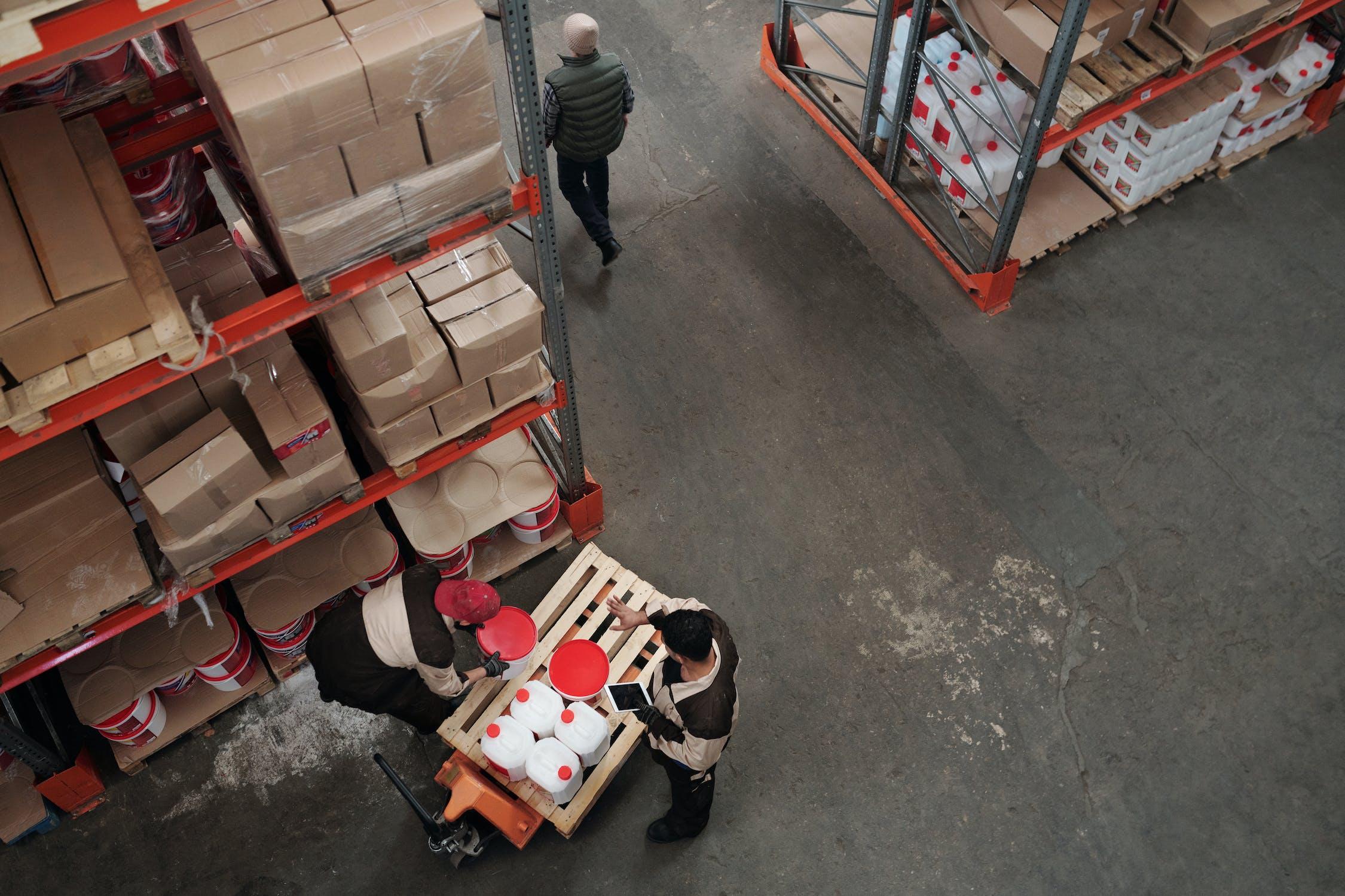 Zwei Personen, die Waren aus dem Regal im Lager nehmen