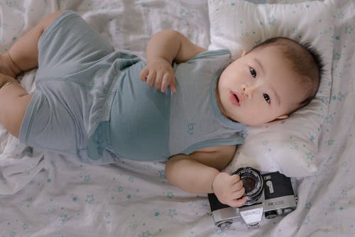 Asian baby playing with photo camera in bed