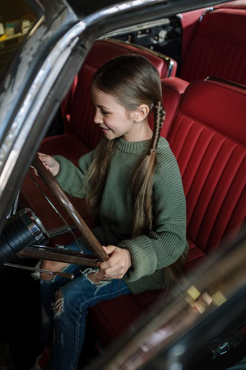 Woman in Green and Brown Striped Long Sleeve Shirt Sitting on Red Leather Vehicle Seat