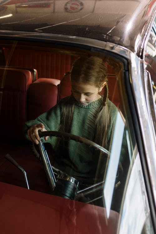 Boy in Green Sweater Sitting on Red Car Seat