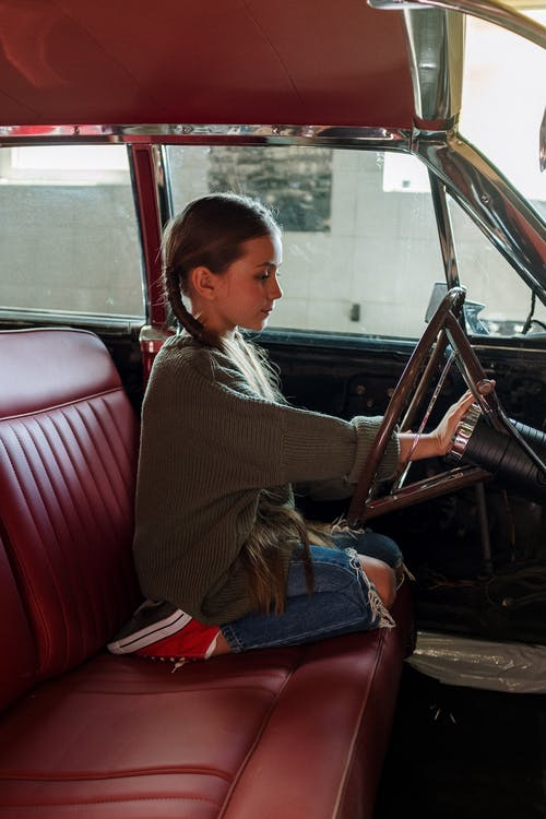 Woman in Gray Sweater Sitting on Red Leather Car Seat
