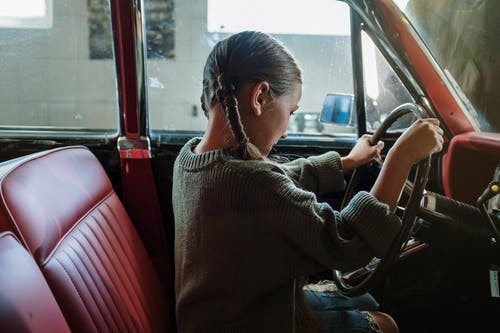 Woman in Gray Sweater Sitting on Red Car Seat