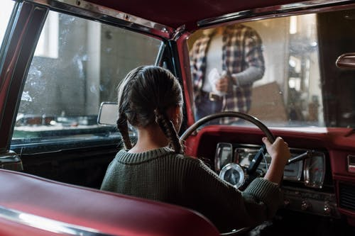 Woman in Black and White Striped Shirt Driving Car