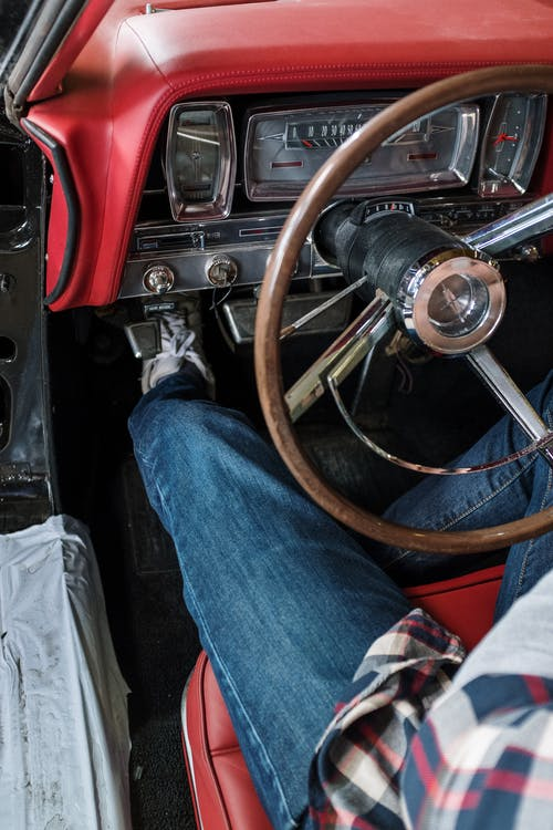Person in Blue Denim Jeans Sitting on Red and Black Car Seat