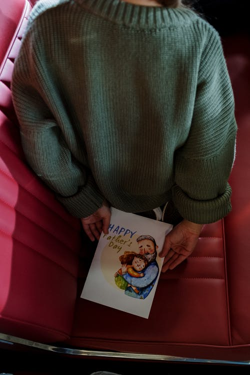 Woman in Green Sweater Holding a Baby Photo