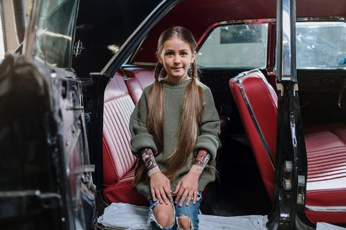 Woman in Brown Sweater and Blue Denim Jeans Sitting on Red Car