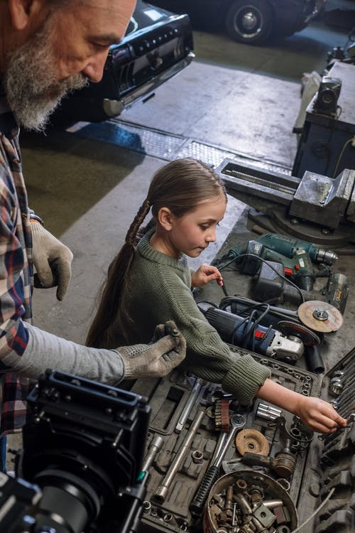 Woman in Green Sweater Holding Black and Gray Motorcycle Engine