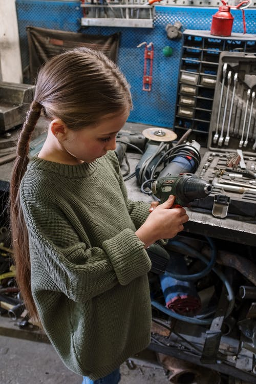Woman in Green Sweater Holding Black and Gray Corded Power Tool