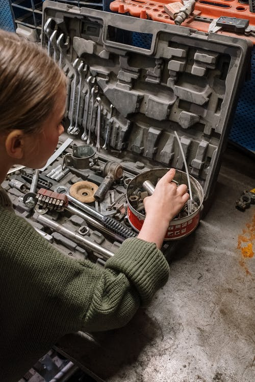 Woman in Green Sweater Holding Gray Metal Tool