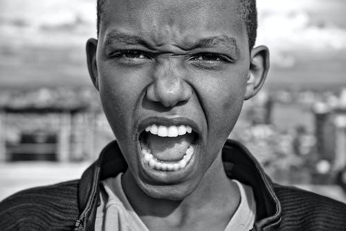 Grayscale Photo of Boy Shouting