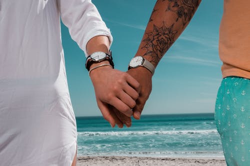 Close-Up Photo of a Couple Holding Each Other's Hands