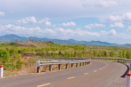 Asphalt road among hilly terrain in highland