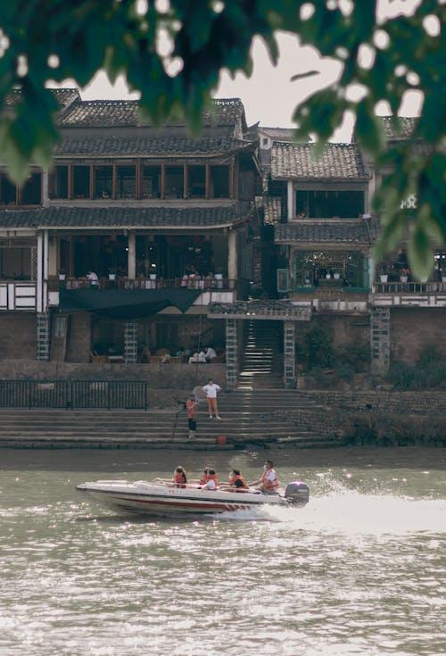 Motor boat floating near old building