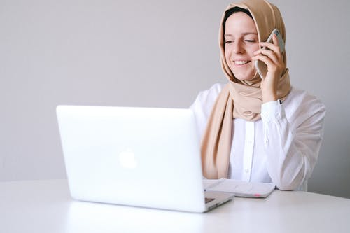 Woman in White Hijab Using Macbook