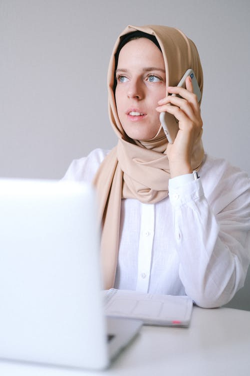 Woman in White Long Sleeve Shirt Using Smartphone