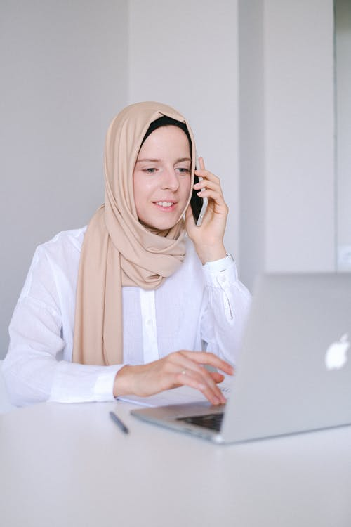 Woman in White Long Sleeve Shirt and Orange Hijab Using Macbook
