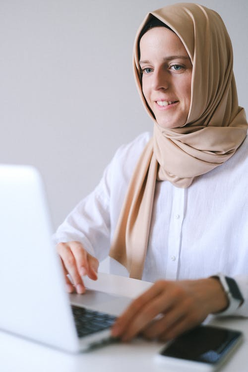 Woman in White Long Sleeve Shirt Wearing Brown Hijab