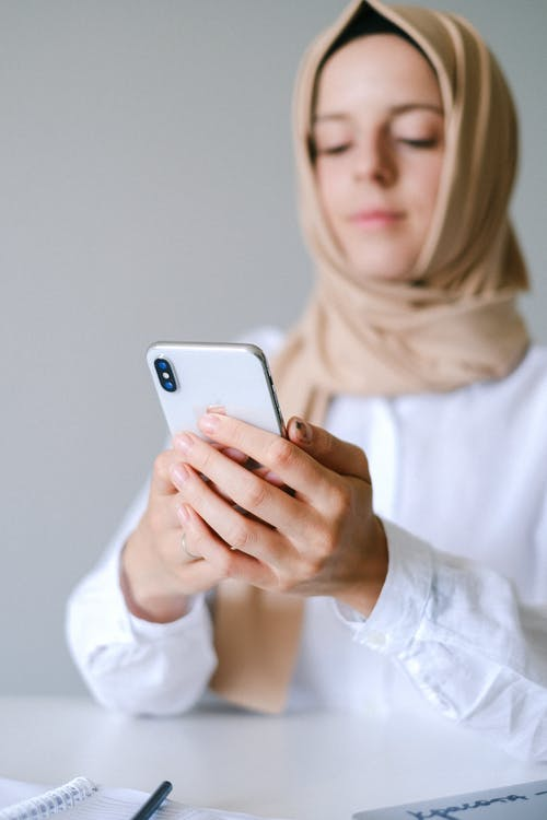Photo of Woman Holding White Smartphone