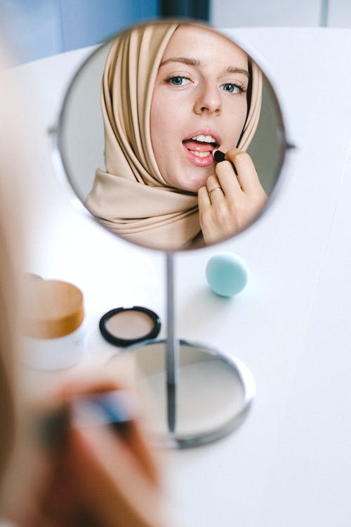 Woman in Hijab Applying Lipstick