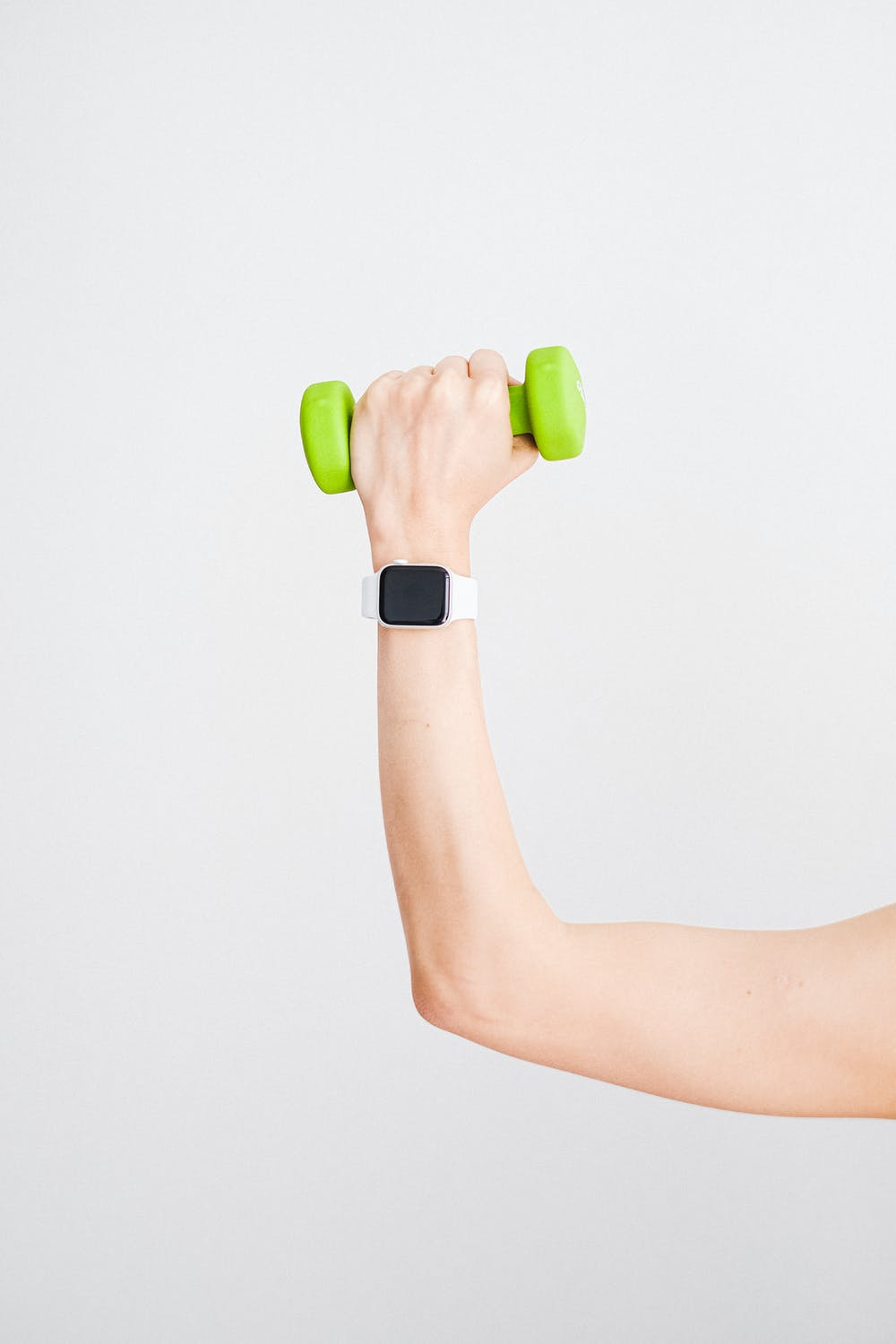 woman flexing with green dumbbell in hand and a sport watch