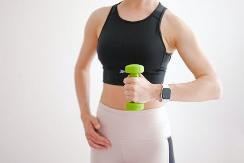 Woman in Black Tank Top Holding Green Dumbbell