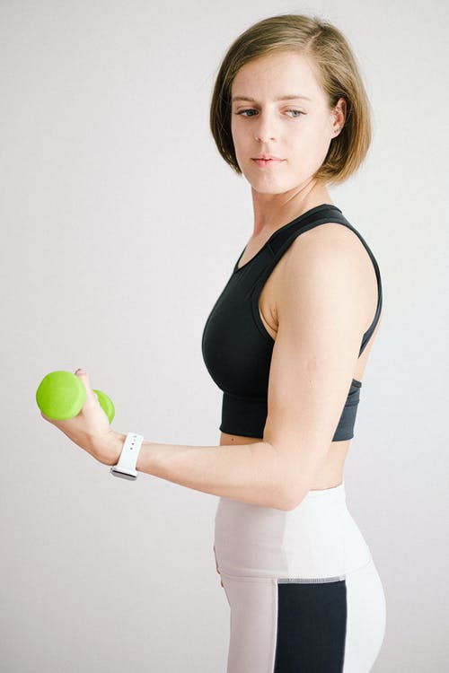 Woman in Black Tank Top and White Pants Holding Green Apple